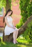 Красивая девушка в белом платье сидя на ветви дерева в парке Стоковое фото RF