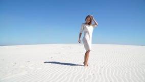 Красивая девушка в белом платье стоя в пустыне видеоматериал