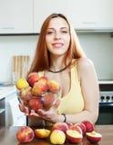 Красивая девушка в желтом цвете ест персики стоковая фотография