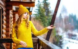 Красивая девушка в желтых свитере и шляпе knit улавливает руки и взгляд снега Стоковые Фотографии RF