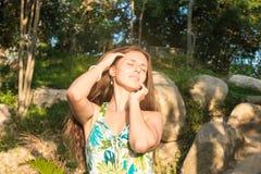 Красивая девушка в зеленом платье на заходе солнца Стоковое Изображение