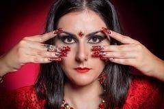 Красивая девушка в изображении индийской женщины в красном сари с ногтями красивой заплаты акриловыми в восточном стиле в студии Стоковая Фотография
