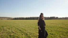 Красивая девушка в длинном черном платье идет на поле сток-видео
