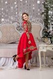 Красивая девушка в красном длинном платье на рождественской елке Стоковые Изображения
