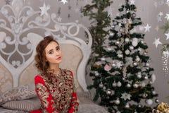 Красивая девушка в красном длинном платье на рождественской елке Стоковое Изображение RF