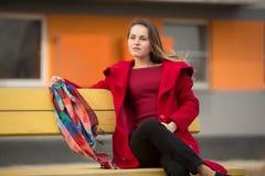 Красивая девушка в красном пальто и стеклах на предпосылке дома стоковые фотографии rf