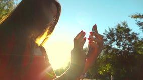 Красивая девушка в красном платье используя ее мобильный телефон в парке, теплые цвета захода солнца Съемка средства замедленного видеоматериал