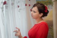 Красивая девушка в красном платье смотрит в окне Стоковая Фотография