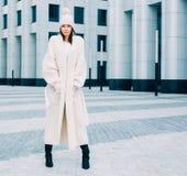Красивая девушка в модных белых пальто и knit представляя на улице Srteetstyle напольно Стоковая Фотография RF