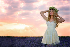 Красивая девушка в поле лаванды на заходе солнца Стоковые Изображения