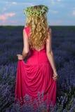 Красивая девушка в поле лаванды на заходе солнца Стоковое фото RF