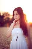 Красивая девушка в пшеничном поле на заходе солнца Стоковая Фотография
