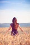 Красивая девушка в пшеничном поле на заходе солнца Стоковые Фото