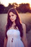 Красивая девушка в пшеничном поле на заходе солнца Стоковое Изображение