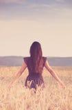 Красивая девушка в пшеничном поле на заходе солнца Стоковые Изображения