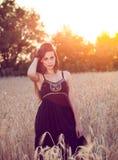 Красивая девушка в пшеничном поле на заходе солнца Стоковые Фотографии RF