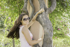 Красивая девушка в платье и солнечных очках стоя рядом с деревом в парке Стоковая Фотография RF