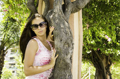 Красивая девушка в платье и солнечных очках стоя рядом с деревом в парке Стоковое Изображение RF