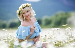 Красивая девушка в платье на поле цветков маргаритки Стоковые Изображения RF