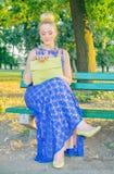 Красивая девушка в платье сидя на стенде Стоковое фото RF