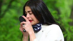 Красивая девушка в плаще белизны красит ее губы с губной помадой видеоматериал