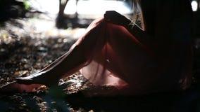 Красивая девушка в свете - розовое платье отдыхая в a сток-видео