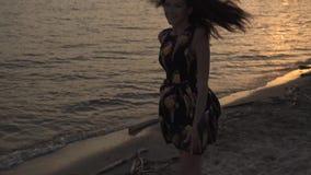 Красивая девушка в светлом платье идя на пляж на заходе солнца и усмехаться сток-видео