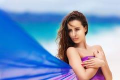 Красивая девушка в фиолетовой ткани на тропическом пляже стоковое фото rf