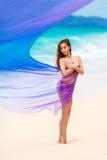 Красивая девушка в фиолетовой ткани на тропическом пляже стоковое фото