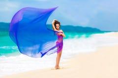 Красивая девушка в фиолетовой ткани на тропическом пляже Стоковые Фото