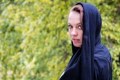 Красивая девушка в черном головном платке в парке стоковое фото
