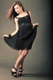 Красивая девушка в черном платье танцует стоковое изображение