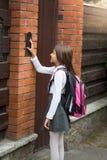 Красивая девушка в школьной форме отжимая кнопку внутренной связи Стоковые Фотографии RF