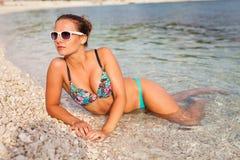 Красивая девушка лежа на побережье и принимая sunbath Стоковые Фото