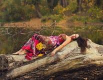 Красивая девушка лежа на стволе дерева Стоковое Изображение RF
