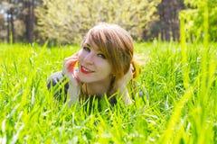 Красивая девушка лежа на траве в парке лета Стоковое фото RF