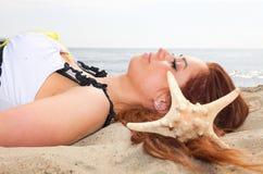 Красивая девушка лежит на морском побережье с каникулами природы раковин стоковое изображение