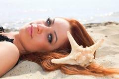 Красивая девушка лежит на морском побережье с каникулами природы раковин стоковые изображения