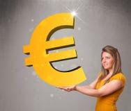 Красивая девушка держа большой знак евро золота 3d Стоковое Фото