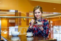 Красивая девушка есть торт в кафе Стоковые Изображения