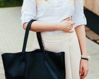 Красивая девушка лета представляя на улице с черной красной супер модной сумкой в белых блузке и юбке на a Стоковые Изображения RF