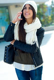 Красивая девушка используя ее мобильный телефон в городе Стоковые Изображения
