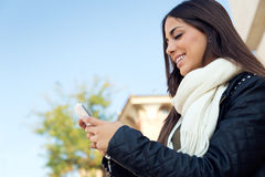 Красивая девушка используя ее мобильный телефон в городе Стоковое фото RF