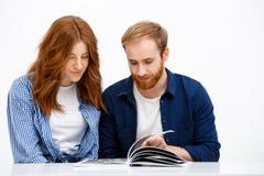 Красивая девушка и мальчик redhead сидя на белой таблице стоковая фотография