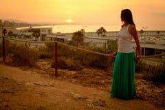 Красивая девушка идя вдоль пляжа на заходе солнца Стоковое Изображение RF