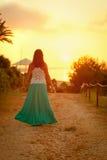 Красивая девушка идя вдоль пляжа на заходе солнца Стоковая Фотография RF