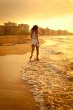 Красивая девушка идя вдоль пляжа на заходе солнца Стоковое Фото