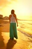 Красивая девушка идя вдоль пляжа на заходе солнца Стоковая Фотография