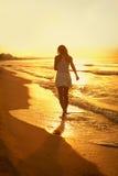 Красивая девушка идя вдоль пляжа на заходе солнца Стоковое Изображение