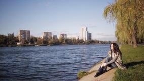 Красивая девушка наслаждается взглядом реки холодный ветер осени развивает ваши волосы мягкий солнечный свет отраженный от воды сток-видео